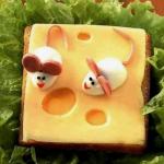 Осторожно нафаршировать яйца полученной начинкой и слепить сверху положить сыр «Масдам» и удобно расположить мышекиз них двух маленьких мышек.